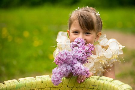 Little lovely girl with a bouquet of lilacs outdoors