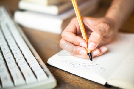 Woman hands writes a pen in a notebook, computer keyboard in background.