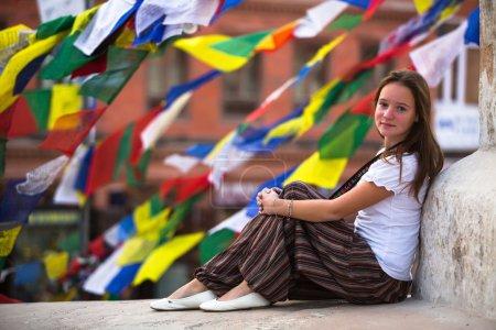 Young girl sitting on Buddhist stupa