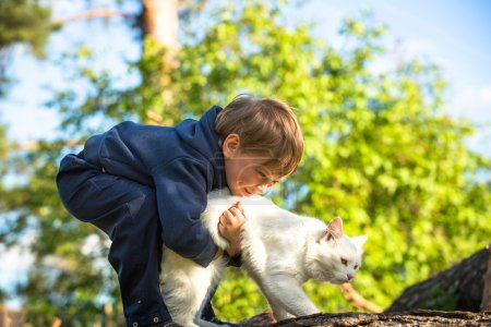 Little boy playing with a cat.