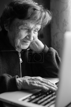 Photo for Elderly woman using laptop computer at home (black and white photo) - Royalty Free Image