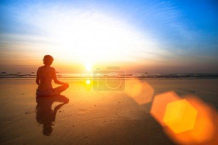 Photo pour Yoga femme assise sur la côte de la mer au coucher du soleil . - image libre de droit