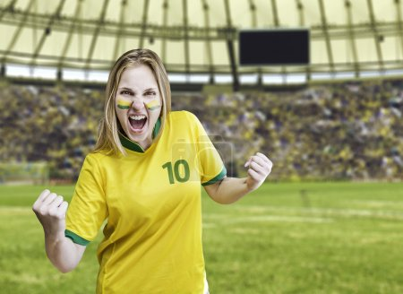Brazilian fan celebrates on the stadium with her face painted