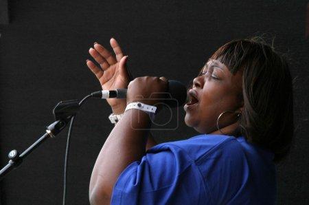 Photo pour Un membre du groupe de gospel les tornades avec révérence chante une chanson d'éloge puissant. - image libre de droit