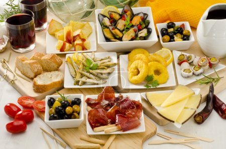 Photo for Spanish cuisine. Assortment of Tapas including Serrano Ham, Manchego Cheese, Marinated Olives, Pikles, Potatoes in Hot Sauce, and others, served with red wine. - Royalty Free Image