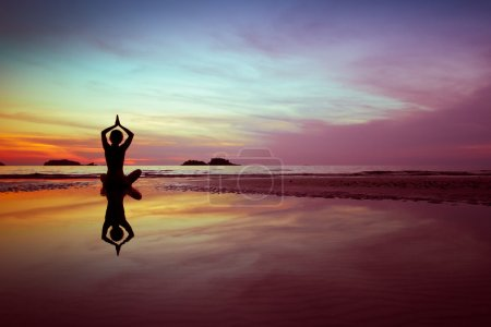 Photo for Woman practices yoga on the beach at sunset - Royalty Free Image