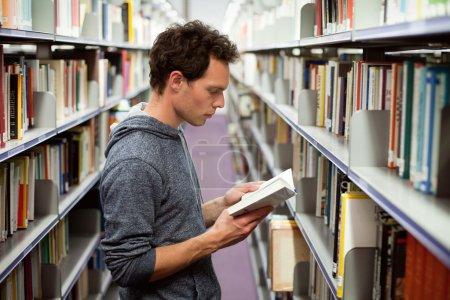 Photo pour Livre de lecture étudiant à la bibliothèque, enseignement universitaire - image libre de droit
