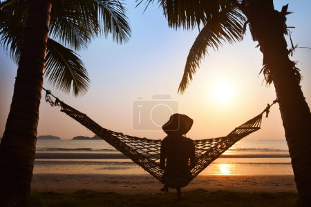 Photo for Silhouette of woman in hat sitting in hammock at sunset on the beach - Royalty Free Image