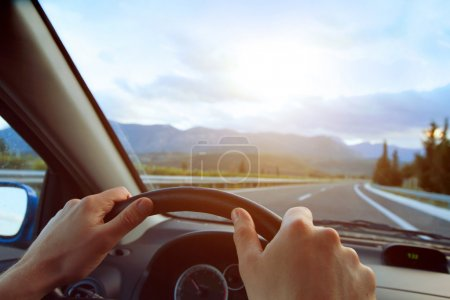 Photo for Hands of a driver on steering wheel of a car and empty asphalt road - Royalty Free Image