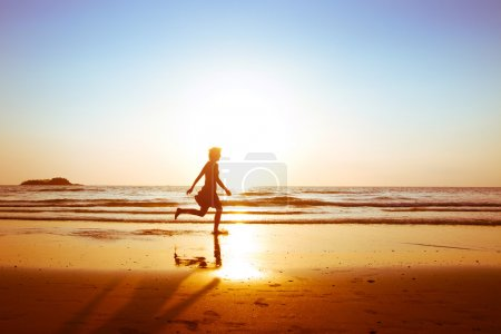 Photo for Silhouette of young happy carefree girl running on the beach at sunset - Royalty Free Image