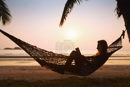 Photo for Silhouette of woman relaxing in hammock on the beach - Royalty Free Image