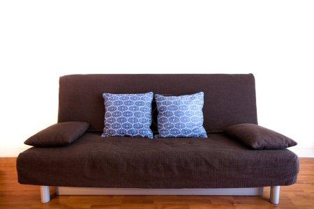 Photo pour Intérieur du studio, canapé noir avec oreillers isolés sur blanc - image libre de droit
