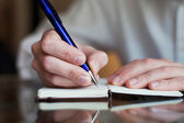 Man writing in the notepad