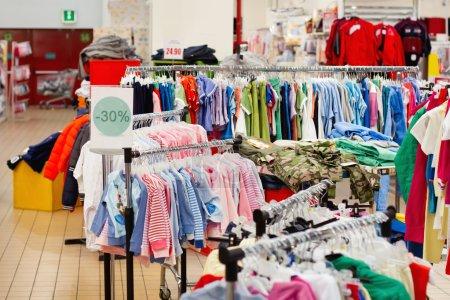 Photo pour Vente de vêtements pour enfants dans le supermarché - image libre de droit