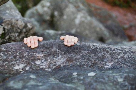 Photo pour Dernier espoir, défi. Les mains accrochées au bord d'une falaise de pierre - image libre de droit