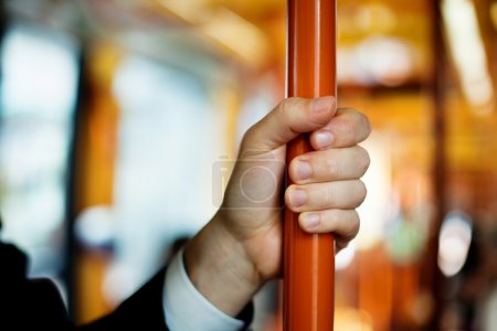 Hand holds handrail in public transport