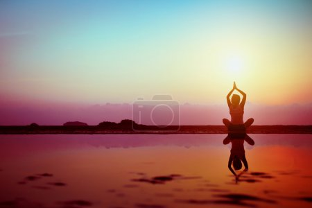 Photo for Silhouette of young woman practicing yoga on the beach at sunset - Royalty Free Image