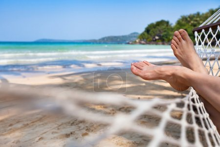 Photo for Woman feet in hammock on the beach - Royalty Free Image