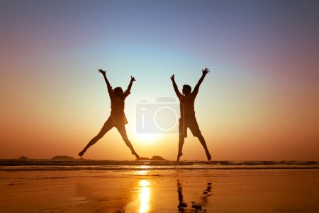 Photo for Family vacations on  the beach, couple jumping - Royalty Free Image