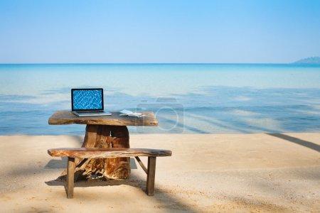 Photo pour Bureau sur la plage, l'ordinateur et la table - image libre de droit