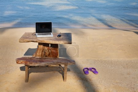 Photo for Perfect work place, laptop on the table on the beach - Royalty Free Image