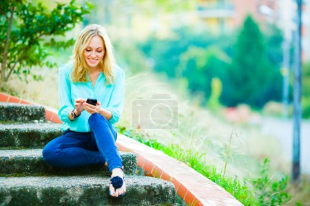 Photo for Happy smiling girl sitting on stairs writing a message on her mobile phone on city park background - Royalty Free Image
