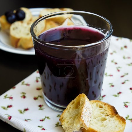 Blueberry jelly in a glass with ship biscuit on a black table view closeup
