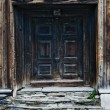 Old double door in wooden house with flagstone doo...