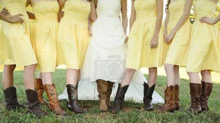 Photo pour Mariée et demoiselles d'honneur montrent leurs bottes à un mariage à la campagne. - image libre de droit