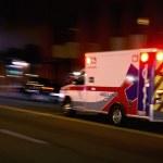 An ambulance speeding through traffic at nighttime...