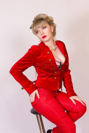 Portrait of a beautiful young blonde girl with short hair in a sexy business style. A woman dressed in a red jacket and red pants.