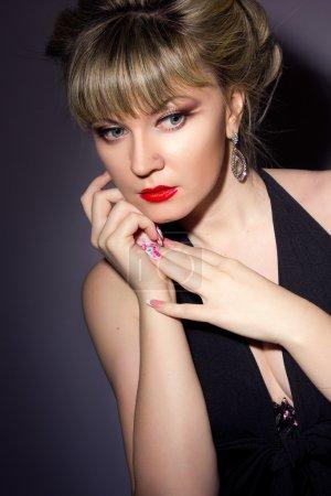 Photo pour Portrait d'une belle jeune femme blonde cuisine avec un maquillage lumineux. Fille habillée en robe de soirée noire sur un fond noir . - image libre de droit