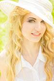 Portrét krásná mladá blondýnka s vlnité vlasy v přírodě. dívka v bílém klobouku sedět na trávě v parku