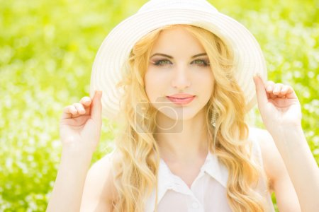 Portrait of a beautiful young blonde woman with wavy hair in nature. Girl in white hat sitting on the grass in the park
