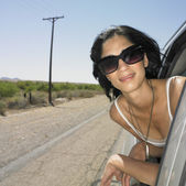 Woman leaning out of car window on deserted road