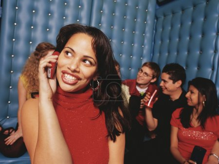 Young woman taking cell phone call in night club