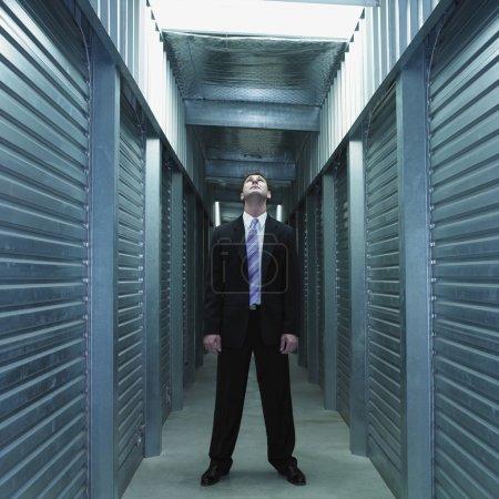 Businessman standing in storage unit hallway