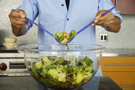 Man in kitchen tossing salad