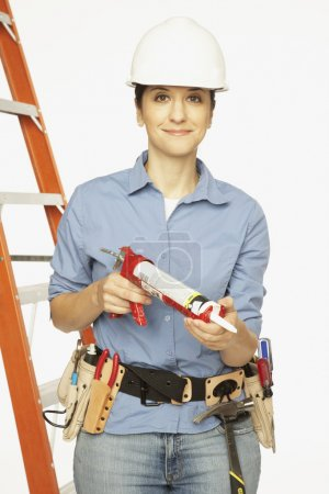 Hispanic female construction worker holding caulking gun