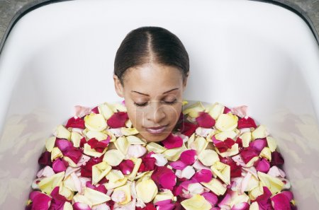 Woman soaking in bathtub filled with rose pedals