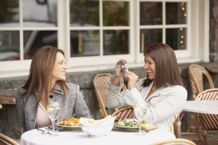 Woman having her photograph taken by other woman at lunch