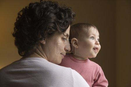 Baby looking over mother's shoulder