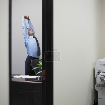 Businessman stretching in his office
