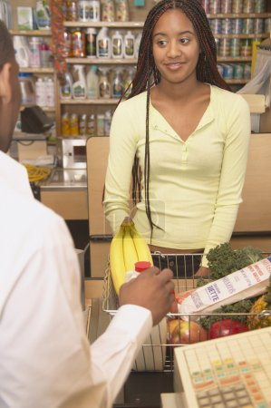African American woman at checkout counter in health food store