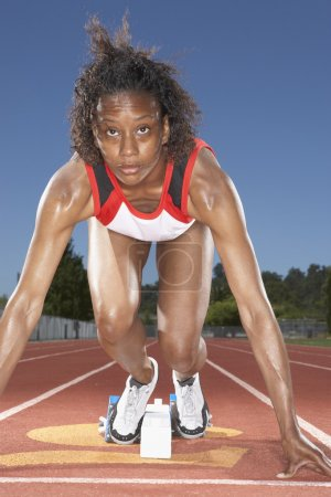 Female track runner preparing to race