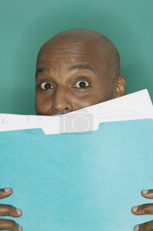 Businessman hiding behind a blue folder