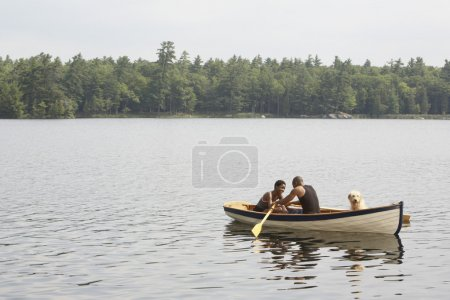 African couple and dog in row boat
