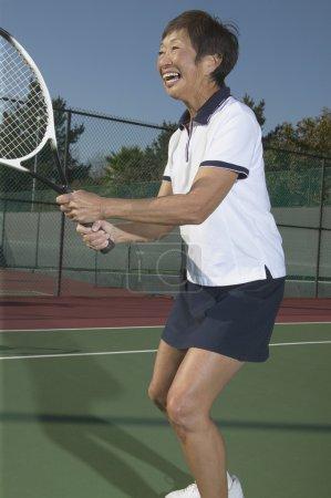 Senior Asian woman playing tennis