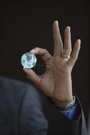 Hand holding small globe