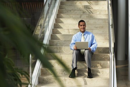 Businessman with laptop sitting on step